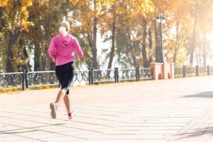 秋の公園でランニングをする女性