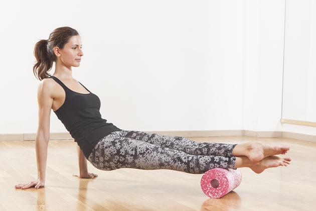 筋膜フォームローラーをする女性